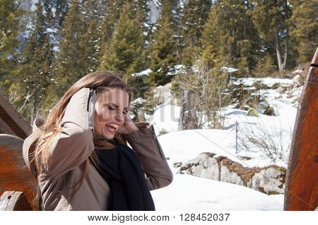 The beautiful brown-haired girl with very loud laughs. Woman laughing very loudly. Happy young girl on vacation in the mountains.