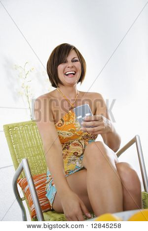 Caucasian mid adult brunette woman holding PDA and smiling.