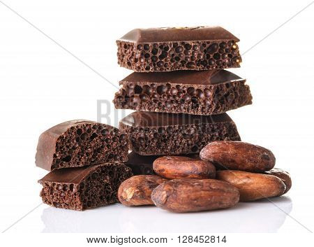 Porous chocolate pieces and cocoa beans on a white background close up