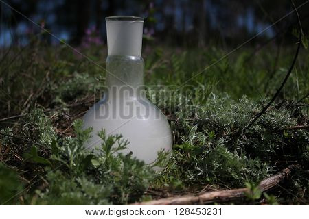 retort with smoke in a green grass