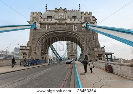 LONDON UNITED KINGDOM - JANUARY 25: Tower bridge landmark with car traffic and people walking across on the sides in London United Kingdom - January 25 2013; Famous London landmark Tower Bridge with cars and people crossing on foot.