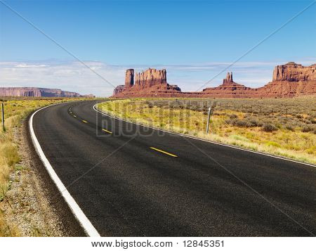 Curve in road in scenic desert road with mesa land formations and mountains.