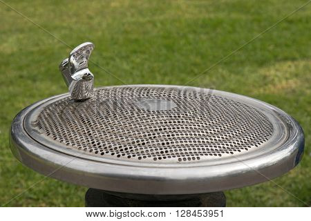 Public free drinking fountain tap, also called water bubbler, provided at the park with blurred green grass background in Melbourne, Australia