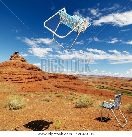 Lawn chair thrown in midair in scenic desert landscape with land formation.