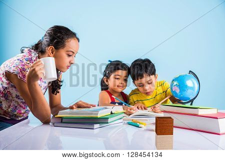 three cute indian kids studying, smart asian girls and boy doing home work, indian siblings studying, indian small girl helping her brother and sister in doing homework