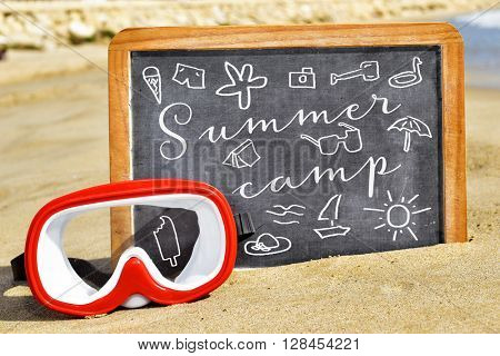 some drawings of summer stuff and the text summer camp written on a chalkboard placed on the sand of a beach next to a red and white diving mask
