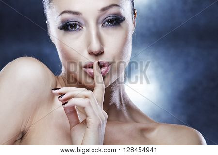 Portrait of a beautiful woman with her finger on lips