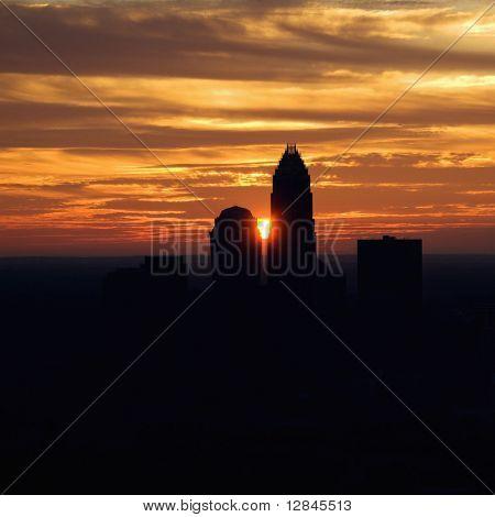 Sunset silhouetting aerial view of Charlotte, North Carolina city skyline.
