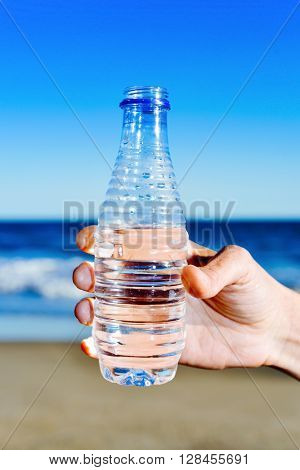 closeup of a young man with a water bottle in his hand in front of the sea