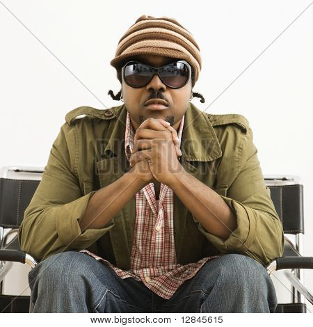 African-American mid-adult man wearing hat and sunglasses and looking at viewer.