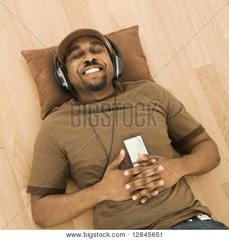 African-American mid-adult man wearing headphones and listening to mp3 player while lying on back on floor.