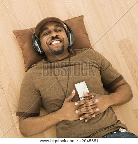 African-American adults tragen von Kopfhörern und anhören der mp3-Player beim liegen am Rücken auf