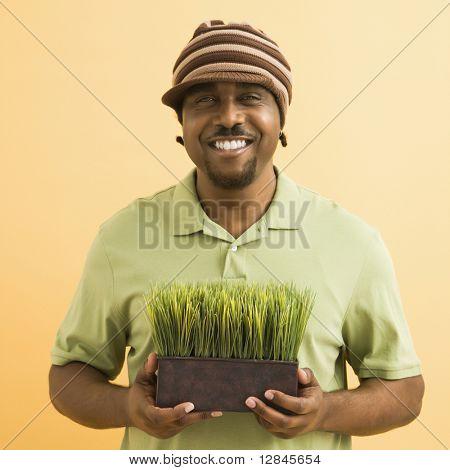 Hombre mid-adult afro-americana que llevaba explotación de sombrero en maceta hierba sonriendo al espectador.