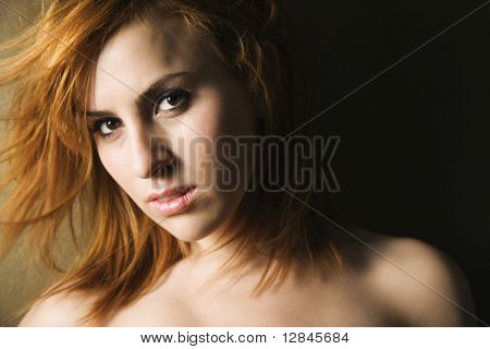 Studio portrait of pretty young redheaded female.