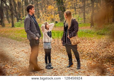 Playfull family of three walk in a park on an autumn day.