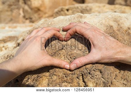 Man and woman making heart shape with their hands on rock.