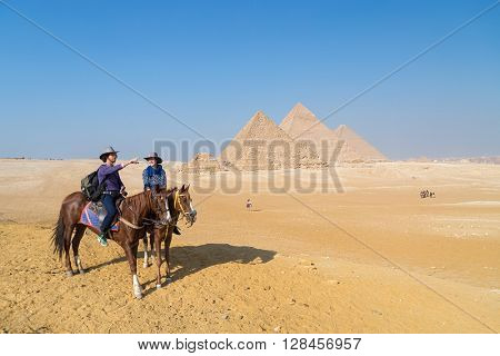 Tourist couple on horseback in front of the Great pyramid of Giza complex, Egypt.