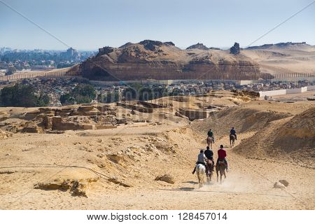 Egyptian tourists riding horses near Great pyramid of Giza, Egypt.