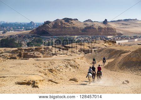Egyptian tourists riding horses near Great pyramid of Giza, Egypt.