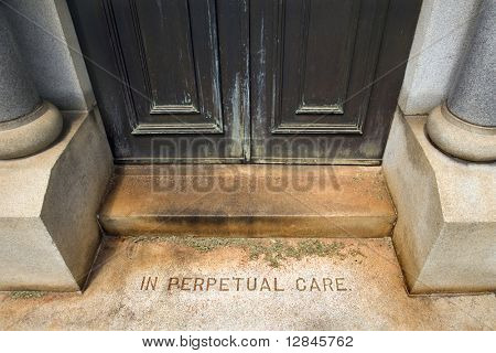"""Entrance to mausoleum in graveyard with words, """"In Perpetual Care"""""""