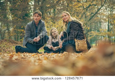 Cheerful family of three kneel on park ground covered with leaves on an autumn day.