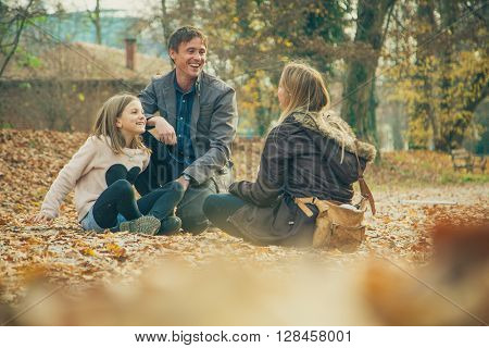 Family of three kneel in park on an autumn day.