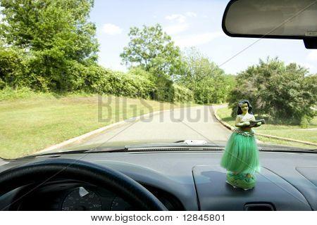 Hula girl on dashboard of car interior.