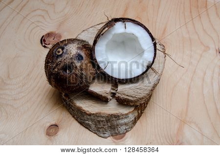Fresh halved brown coconut on light wooden background. Organic healthy food concept. Beauty and SPA. Eco nature style. Rustic wallpaper.