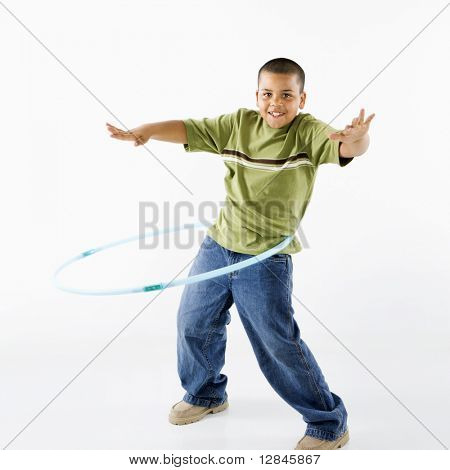 Young latino adolescent boy using hula hoop.
