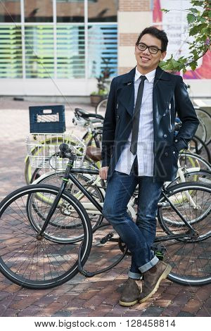 Young smiling asian business man or student standing in front of bicycle parking rack on city street