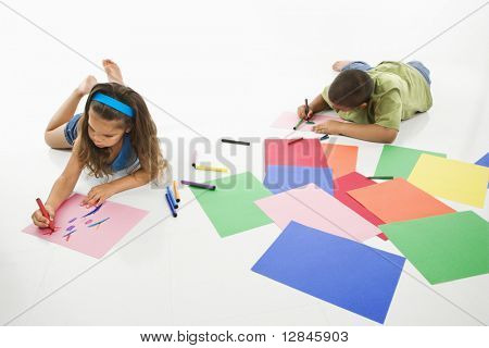 Young latino boy and girl coloring on construction paper and smiling.