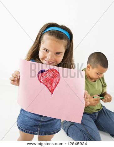 Young girl showing off drawing of heart while boy sits behind her.