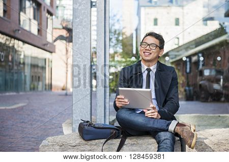 Young smiling asian business man holding a digital tablet sitting outside on city street looking away