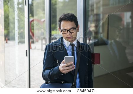 Young serious asian business man looking at mobile phone outside on city street near building
