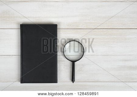 Flat lay of black notebook and magnifying glass on light wooden surface. Composition. Office workplace. Office stuff. Workplace of geologist, physician, archaeologist, banker, criminalist or jeweler. Optical system. Research and investigation. Deep scan.