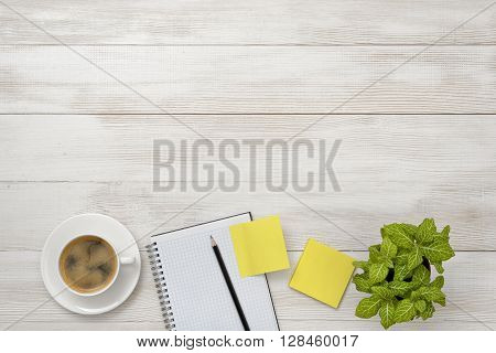 Cup of coffee, indoor plant, empty notebook with pencil and stickers. Top view composition. Workplace of office man. Willingness to work overtime. Increasing productivity in the mornings. Keeping healthy. Contribution to wellbeing. Reducing stress. Improv