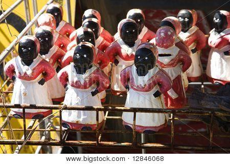 Auflistung von Aunt Jemima Statuetten auf Regal.