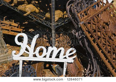 Metal garden decoration of word Home next to rusted metal objects.