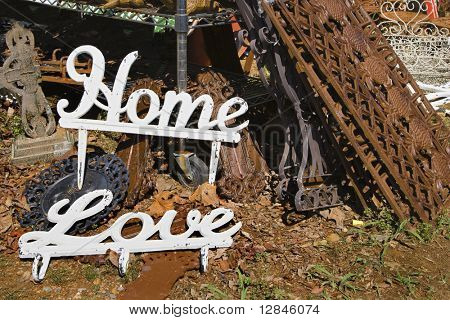 Metal garden decorations of words Love and Home next to rusted metal objects.
