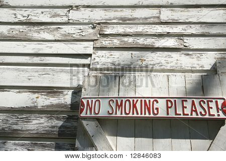 """Sign on old white peeling building reading """"No smoking please!""""."""