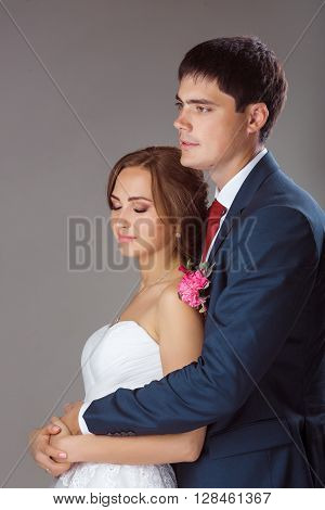 Studio portrait of young elegant just married bride and groom and  embracing on grey background