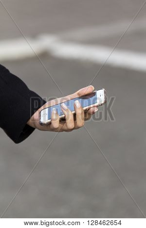 girl with French manicure keeps mobile phone