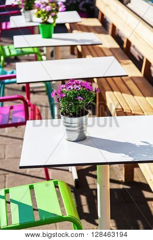 tables and chairs of a sidewalk cafe with flower decoration