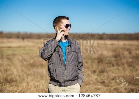 Young man with sunglasses and windbreaker talking on the mobile phone. There is a  field as background.