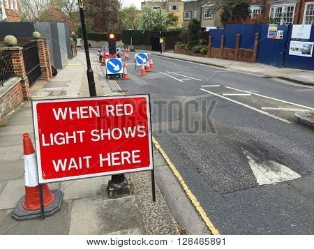LONDON - MAY 3: Traffic lights, signs and cones at temporary roadworks on May 3, 2016 in Hampstead, London, UK.