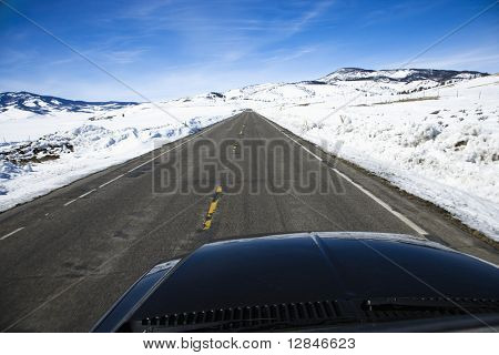 Perspective shot of car driving down road in snowy Colorado during winter.