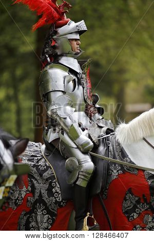 Harcourt France - April 23 2016: An unidentified man in a suit of armour is riding his horse to a mediaeval jousting tournament on Apr. 23 2016 in Harcourt France. It takes place in front of the castle Harcourt