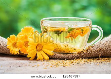 Cup of marigold tea and calendula flowers outdoors on green background.