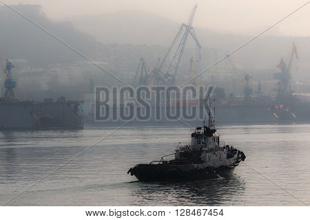 tugboat sailing in the port town in the background in the fog