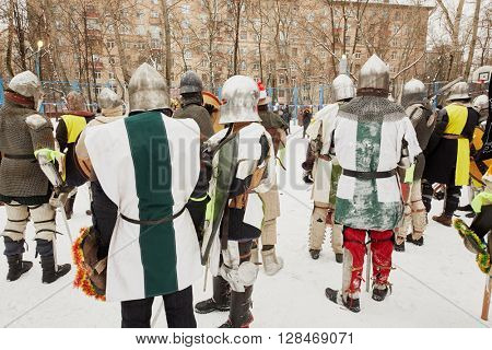 RUSSIA, MOSCOW - DEC 28, 2014: Men dressed in warriors defensive equipment and spectators during historic reenactment battle on Military History maneuvers on Taganka.